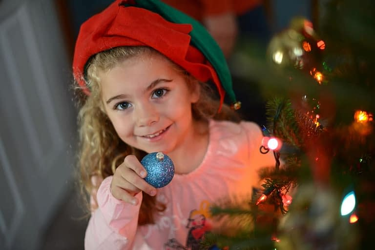 Here the photographer added interest to the image by having the subject hold an ornament. The focus is placed on the girl, allowing for some of the holiday lights to blur in the foreground. Photo by: Melissa DiBartolo