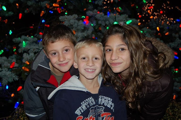 You can take great portraits of your kids outdoors, using the holiday lights that are hung on trees and bushes outside your home as a background. Here the photographer used a shutter speed of 1/60 of a second and f/4.5 aperture. A flash was used to light up the kid's faces. By adding space between the subject and background, the colorful lights are not blown out but keep detail and in the far background the photographer was able to retain a nice bokeh effect. Photo by: Elizabeth Barbieri
