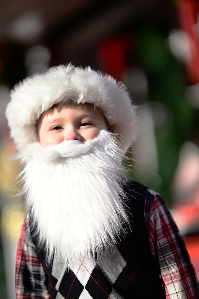 Talk about cute! This young boy posed for the camera wearing a pint-sized Santa beard and hat. Photo by: Marc Cutler