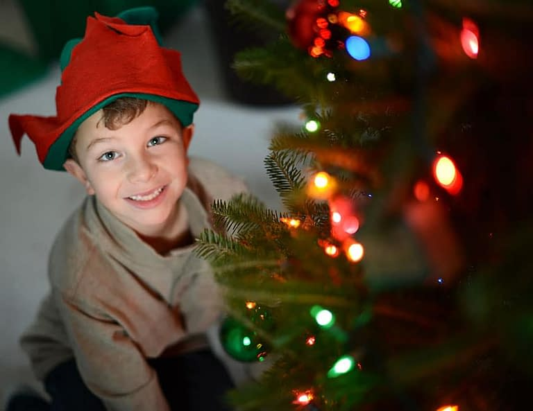 This is a great holiday portrait of a young boy. The focus is placed on the boy, allowing for some of the holiday lights to blur in the foreground. Photo by: Melissa DiBartolo